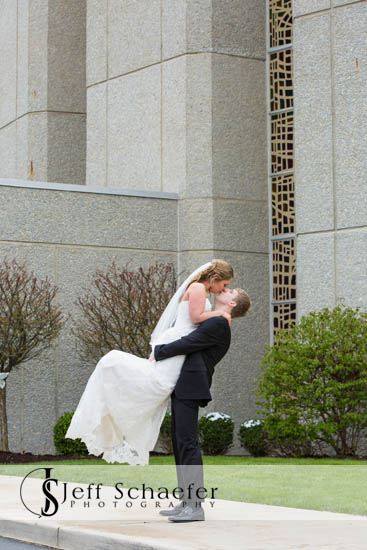 Groom gives the bride a fun lift outside of Incarnation Church Dayton Ohio